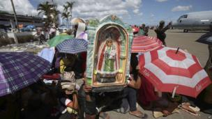 Typhoon survivor Rodrigo Villajos uses a figure of the Our Lady of Manaoag to shield him from the heat of the sun as he waits with others for the next military plane flight to Manila at Tacloban airport in Leyte province, central Philippines, 15 November 2013