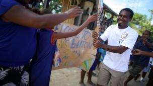 A batonbearer carries the Queen's Baton past local children who made handmade signs to welcome its arrival in Honiara, Solomon Islands.