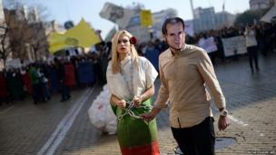 A student wearing a mask of Bulgarian Prime minister Plamen Oresharski pulls another chained student during an anti-government protest in Sofia
