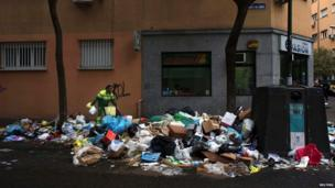 A street cleaner picks up a trash on the first day of regular service after a 13-day strike by street sweepers in Madrid on 18 November 2013