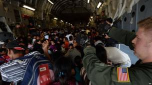 Typhoon victims are loaded onto a US Air Force C17 Cargo plane before being evacuated to Manila, at Tacloban airport in the aftermath of Typhoon Haiyan on 18 November 2013