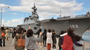 Relatives of Japanese troops aboard the helicopter destroyer Ise, wave as the ship leaves port at Kure base in Kure, western Japan, on 18 November 2013