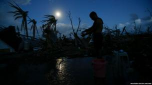 A survivor of Typhoon Haiyan bathes under full moon in the early morning hours, near the airport of the eastern Samar city