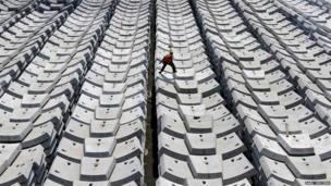 A worker walks over giant pieces of concrete that will be used to make tunnels in Chennai, India