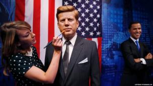 Clare Calvin, a colouring assistant with Madame Tussauds tourist attraction, poses for photographers next to the wax figures of the President, John F Kennedy and President Barack Obama