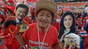 """Thai pro-government """"red-shirts"""" hold pictures of Thaksin and Yingluck Shinawatra as they gather at Rajamangala stadium in Bangkok, 24 November 2013"""