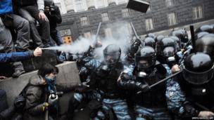 Protesters use tear gas and throw stones during clashes with riot police in Kiev, Ukraine
