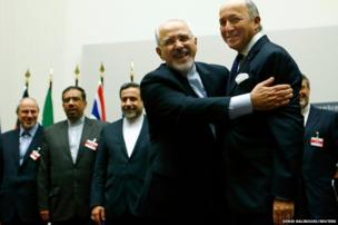 Iranian Foreign Minister Mohammad Javad Zarif hugs French Foreign Minister Laurent Fabius