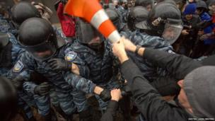 A protester clashes with riot police during a rally supporting EU integration in front of the Ukrainian cabinet of ministers building in Kiev.
