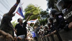 Anti-government protesters face riot police outside the headquarters of the Puea Thai Party of Prime Minister Yingluck Shinawatra in Bangkok, 29 November 2013