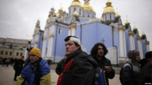A wounded protester stands in front of St Michael's cathedral with the European Union flag in Kiev.