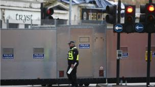 An officer walks past a police cordon set up around the site of a helicopter crash on a pub in the centre of Glasgow