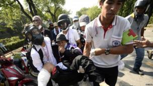 An anti-government protester, who was hit with a rubber bullet fired by Thai riot police, is carried by medical staff outside Government House in Bangkok, 2 December 2013