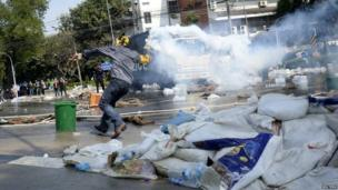 An anti-government protester throws a tear gas canister at Thai riot police as they attempt to remove barricades outside Government House in Bangkok, 2 December 2013