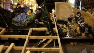 Protesters rest on a barricade at Independence Square 02/12/2013