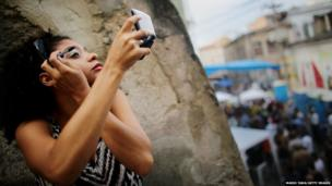 Agatha Rosa applies her makeup before dancing during the National Day of Samba celebrations in Brazil