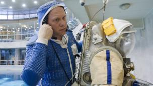 Russian cosmonaut Oleg Artemyev puts on a spacesuit ready for an underwater training session in a pool near Moscow on December 4, 2013.