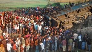 Bangladeshi onlookers gather at the scene of a derailed train in Gaibandha, on December 4, 2013.