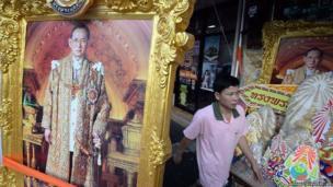 A Thai man walks past paintings of King Bhumibol Adulyadej at a side street on the eve of his birthday in Bangkok on December 4, 2013.