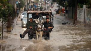 Palestinians ride a cart through a flooded street
