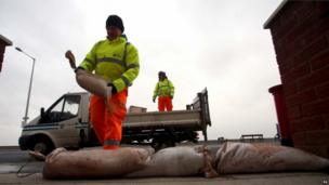 A council worker piles sandbags in front of a building