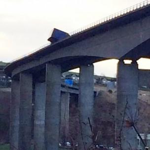 A lorry on its side on a bridge, part of it hanging over the edge