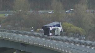 Lorry on its side on bridge