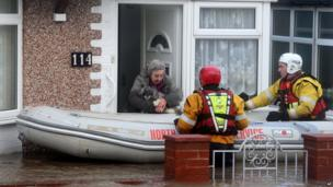 A woman and her dog are rescued by the RNLI or Royal National Lifeboat Institute, from floods as heavy seas and high tides sweep across the country, in Rhyl, Wales