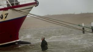 Man secures his boat on the west coast of Jutland, Denmark (5 Dec)