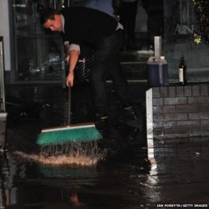 A member of staff in a pub in Whitby tries to clean out flood water from the bar