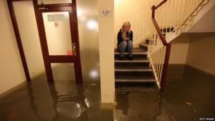 Woman sits on stairs above flood water
