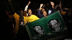 South Africans hold pictures of former South African president Nelson Mandela