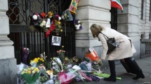 A woman lays a floral tribute for former President Nelson Mandela at the South African High Commission in London