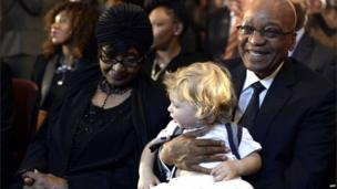 Winnie Mandela and President Jacob Zuma, holding a child, in Bryanston Methodist Church, Johannesburg (8 Dec 2013)