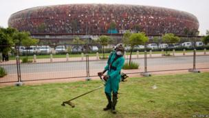 A worker trims the grass outside the FNB stadium in Johannesburg