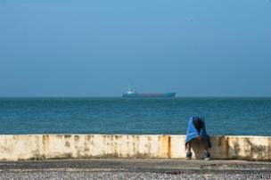 A man sits on the sea wall