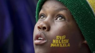 """A boy with """"Rest In Peace Nelson Mandela"""" painted on his face looks up to the skies during the memorial service."""
