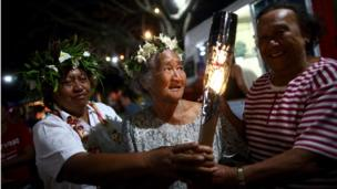 Members of the local community hold the Queen's Baton at a local beach market in Rarotonga, Cook Islands.