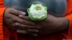 A Thai Buddhist monk holds a flower