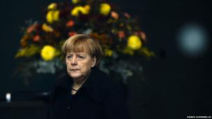 German Chancellor Angela Merkel stands in front of a bunch of flowers in the foyer of the chancellery as she waits for the arrival of the Prime Minister of Norway, Erna Solberg, in Berlin, Wednesday, Nov. 20, 2013.