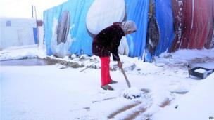 A Syrian refugee shovels snow outside her tent in the makeshift refugee camp of Terbol near the Bekaa Valley town of Zahleh in eastern Lebanon on December 11, 2013