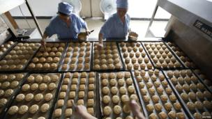 Freshly-baked mooncakes pass along a conveyor belt at a mooncakes factory in Shanghai, 12 September 2013