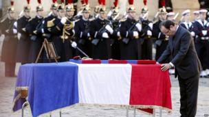 French President Francois Hollande (R) pays his respect in front of the flag-draped coffin of one of the two military that died on December 9 in Central African Republic, during a ceremony in the courtyard of the Invalides in Paris