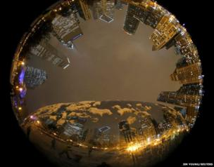 Chicago skyline is reflected in the bean-shaped mirrored sculpture