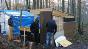 Roma people rebuilding huts after their camp was destroyed