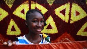 Fatim Fofana, 15, poses for a picture with dyed textile material in Air France 2, a neighbourhood in Bouake, Ivory Coast, on 14 December 2013