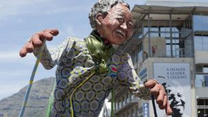 A giant puppet of Nelson Mandela parades in the street of Cape Town, South Africa, on 16 December 2013