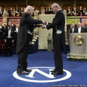Peter Higgs (L) of Britain receives his Nobel Prize in Physics from Sweden's King Carl Gustaf during the 2013 Nobel Prize award ceremony in Stockholm December 10, 2013.
