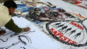 "In this photograph taken on December 30, 2012, Indian bystanders write on a banner featuring images of ""government and rapists"" as it lies on a road in New Delhi, after the cremation ceremony for a gangrape victim."