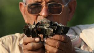 A villager shows mortar shells, that locals say are being fired from the Pakistan side of the international border, at a village in Samba sector, about 75 km (47 miles) from Jammu October 21, 2013.